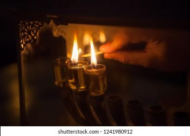 Jewish man macro lighting traditional Hanukkah olive oil candles menora in Israel