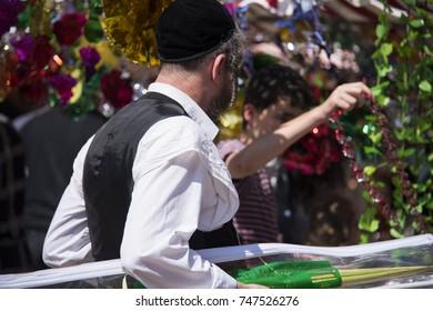 Jewish man wearing kippah. Sukkot's four species festival. Palm branch. Sukkah decorations