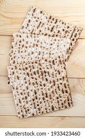 Jewish matzah on wooden rustic background. Jewish traditional Passover bread. Pesach celebration symbol. Close up