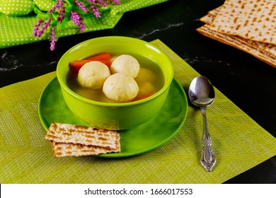 Jewish matzo ball soup on table with matzos bread for Passover.