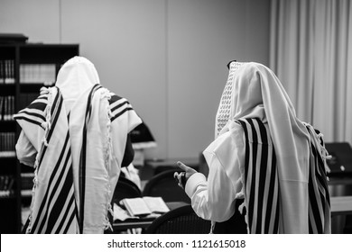 Jewish men covered in prayer shawls stand by dais with prayer books during morning prayers in black and white