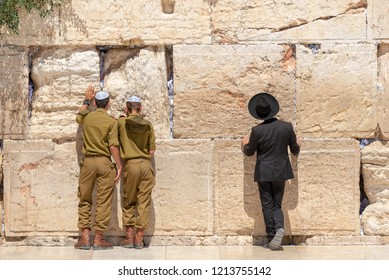 Jewish orthodox believers reading the Torah and praying facing the Western Wall, also known as Wailing Wall or Kotel in Old City in Jerusalem, Israel. It is small segment of the structure which origin