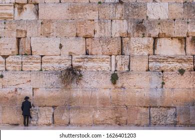 A jewish orthodox man standing at the Western Wall in Jerusalem, Israel.