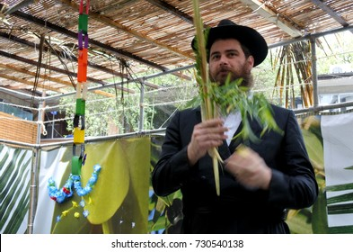 Jewish Orthodox Rabbi blessing on the Four Species in a Sukkah on sukkot Feast of Tabernacles, Feast of the Ingathering or Feast of booths.