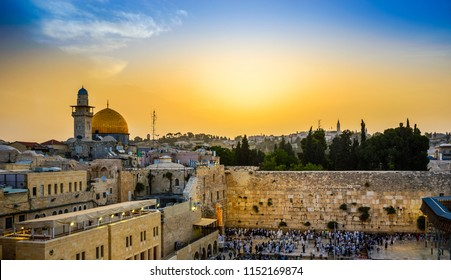 Jewish people gather for Shacharit sunrise prayer at the Western/Wailing Wall, the holiest place in Judaism, with the muslim Dome of the Rock, the Temple Mount and Mount of Olives in the background