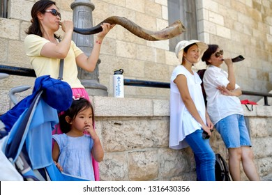 A  Jewish Pilgrim trumpets into a shofar - a Jewish ritual brass musical instrument at the background of the Wailing Wall and old city of Jerusalem.   Israel. 14 September 2015