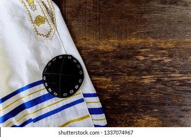 Jewish prayer items tallit and kippa on a wooden table