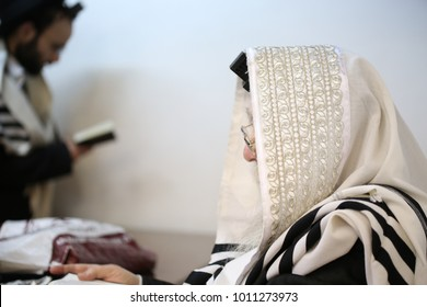 Jewish Rabbi prays the morning prayers with his Tallit and Tefillin in synagogue