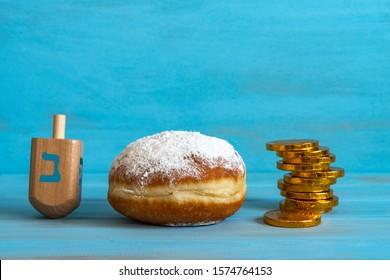 Jewish symbols of Hanukkah (sufganiya, dreidel, chocolate coins) on blue background with copy space.