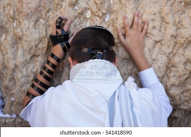 jewish teenager celebrate bar mitzvah at the wailing wall and praying with hands on the stones
