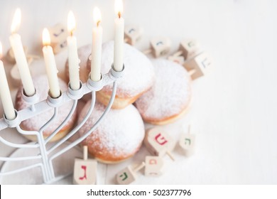 Jewish traditional holiday Hannukah with menorah, doughnuts and dreidles. Copy paste background.