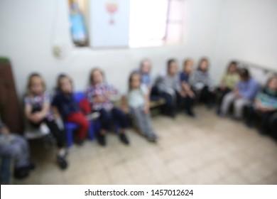 Jewish ultra orthodox boys sit in a half circle in their school classroom, blurred