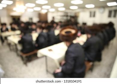 Jewish ultra orthodox hasidic men sit and learn Torah in a Yeshiva study hall