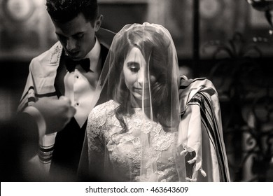 Jewish wedding. Black and white picture of groom covering with his shawl bride's shoulders