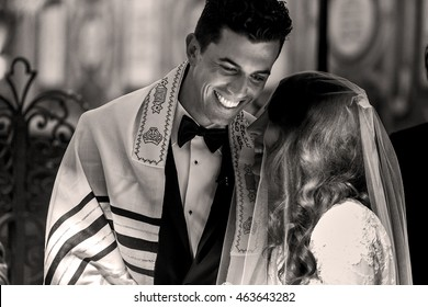 Jewish wedding. Smiling groom bends to the bride