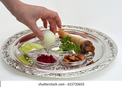 Jewish woman hand organizing Passover Seder Plate with The seventh symbolic item used during the seder meal on passover Jewish holiday.