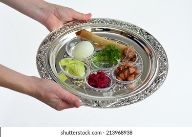 Jewish woman hands carry Passover Seder Plate with The seventh symbolic item used during the Seder meal on Passover Jewish holiday. On white background with copy space
