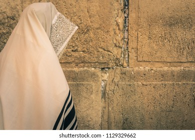 A Jewish worshiper praying at dawn in front of  the Western Wall in Jerusalem, Israel.