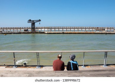 Jewish young couple (man wearing kippah and woman with head scarf) relaxing in sunny spring day at Tel Aviv port, Israel. Back view; unrecognizable people. Tel Aviv port is popular local leisure spot.