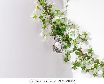 Jewlery elements diamond crystal necklace on pure white background with white spring flower with light green leaves on a light pink vase.