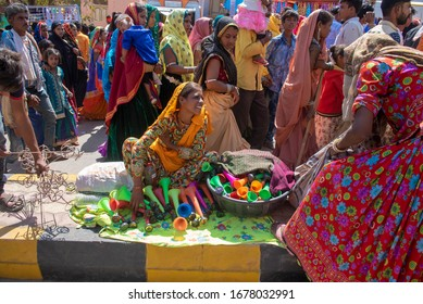 Jhabua  / India 8 January 2020 Indian tribal woman selling trumpet Hooter Horn at a local india market in the town of  Jhabua during Bhagoria Festival in Madhya Pradesh India
