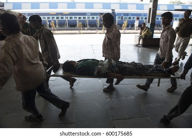 Jhansi / India 26  February 2017  People carry an injured man on a stretcher at Jhansi Railway station uttar pradesh  India