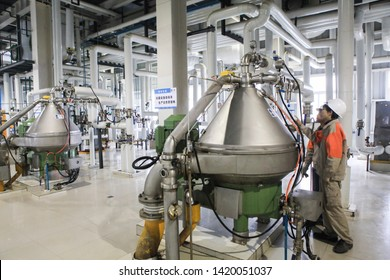 Jiangxi, China - March 3, 2019: blue-collar workers operate machinery at cofco's soybean oil production plant. The trade war triggered a 70 per cent drop in Chinese soyabean imports from the us.