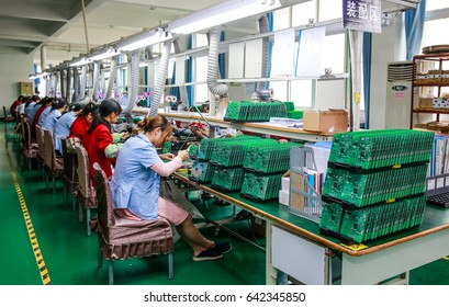 JIANGXI CHINA-May 13, 2014: Jiangxi Shanshui Photoelectric Co., Ltd. research factory workshop, information engineers are developing computer chips, electronic workers put chips on the circuit board.