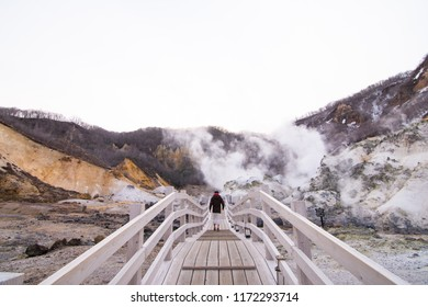 Jigokudani or Hell Valley in the town of Noboribetsu Onsen Hokkaido, Japan, hot steam vents, sulfurous streams. The man is standing on the wooden bridge which show a perspective view.