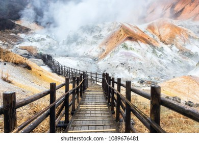 Jigokudani hell valley walking trail with visitors covered by dense sulfur gas during raining, Noboribetsu Hokkaido, Japan. Famous natural travel destination with Hot spring stream water.