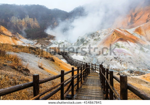 Jigokudani hell valley wet wooden walking footpath trail with enormous sulfur mist during raining in Noboribetsu, Hokkaido, Japan. The air smell here is pretty bad due to heavy sulfur gas.