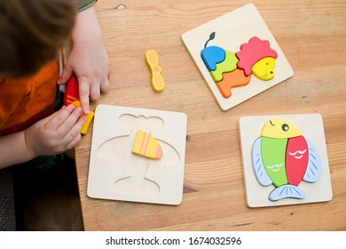 Jigsaw Baby Early Educational Toys 3D Puzzle Children Ability Exercise Kids Wooden Gifts. Boy hand on puzzle part. Early education, focus exercises