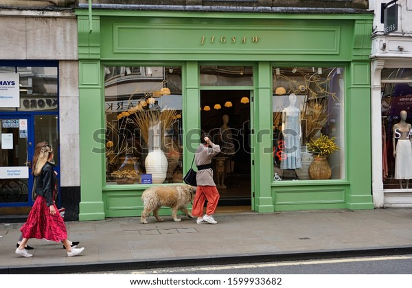 JIGSAW cloths and fashion shop, Oxford, England. People and a dog walking by the shop. Photo was taken on 05/06/2019.