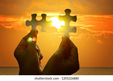 Jigsaw connecting by hand on sunrise orange sky. The concept of team work together connectivity business.