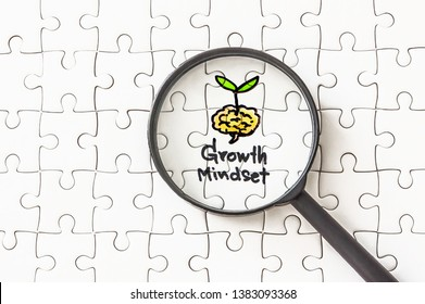 Jigsaw and magnifying glass with concept of growth mindset