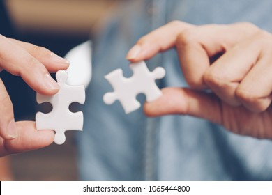 jigsaw puzzle holding by two people hands, together to success concept