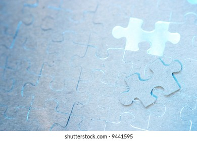 A jigsaw puzzle missing one piece with blue light showing through from below.