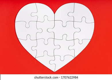 Jigsaw puzzle pieces in form of heart on red background. Love, charity, donation, helping concept. Perfect match, reunion.