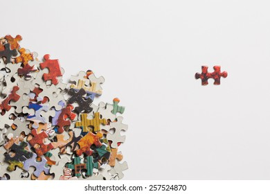 Jigsaw puzzle pieces in a pile with a single piece separated on a white background