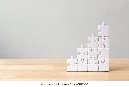 Jigsaw puzzle stacking as step stair on wooden table. Business concept for growth success process