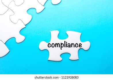 Jigsaw puzzle with word ' compliance' on blue background. Conceptual image.