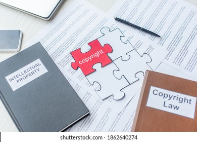 Jigsaw puzzles with copyright lettering on workplace with paperwork and books