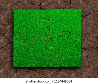 Jigsaw puzzles of green grass texture, on dry red soil background, high angle view.
