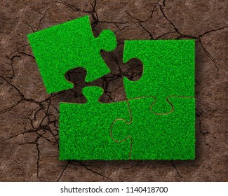 Jigsaw puzzles of green grass texture, on dry red soil with cracks background, high angle view.