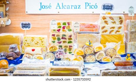 Jijona, Valencia / Spain - 12 08 2017: Spanish christmas sweet and turrones at Jose Alcaraz Picó at decorated christmas market with lights at night in Jijona, Alicante, Spain.