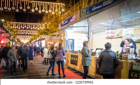 Jijona, Valencia / Spain - 12 08 2017: People buy turrones at Turrones 1880 tent at decorated christmas market with lights at night in Jijona, Spain. Famous city with turrones in during holidays.