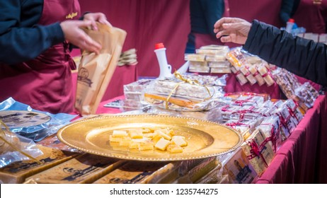 Jijona, Valencia / Spain - 12 08 2017: People buy turrones at Ana Sirvent tent at decorated christmas market with lights at night in Jijona, Spain. Famous city with turrones in during holidays.