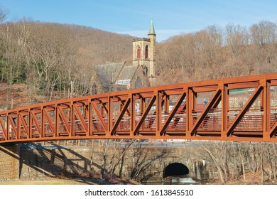 Jim Thorpe, PA - December 24, 2020: Photo of walking bridge over Lehigh River with church in the background.