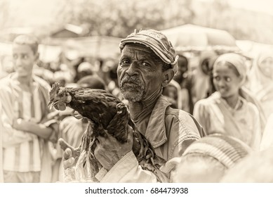 JIMMA, ETHIOPIA - MAY 2, 2015 : Old ethiopian man selling a rooster in a market. Vintage black and white processed.