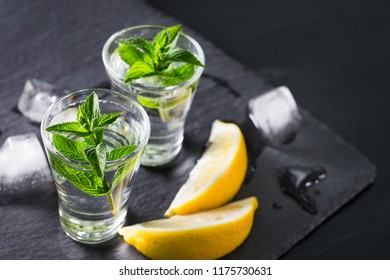 Jin or vodka with mint slices of lemon and ice on a black background. Alcohol cocktail with citrus and herbs. Copy space